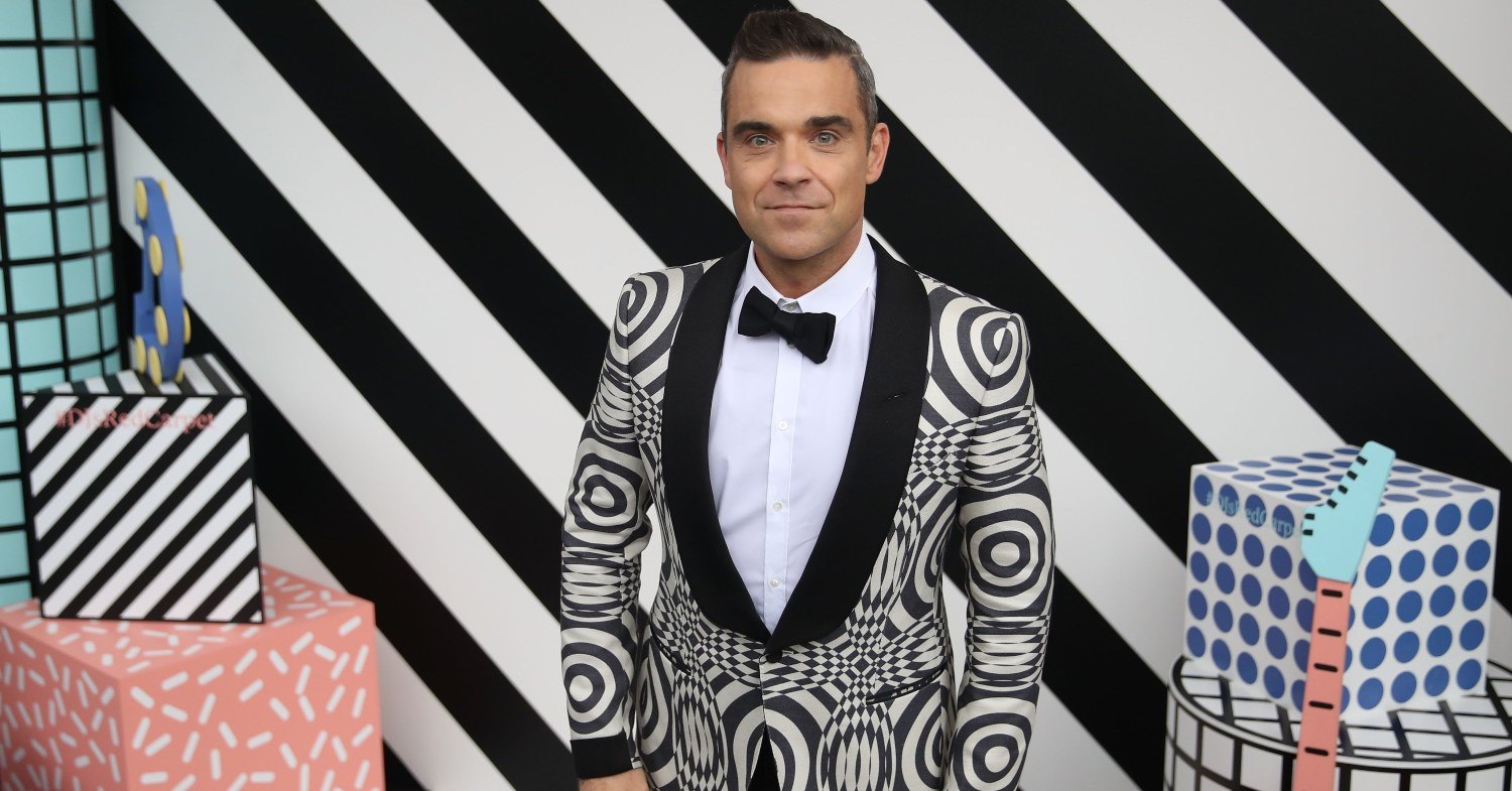 Robbie Williams stands at an event against a black and white striped background