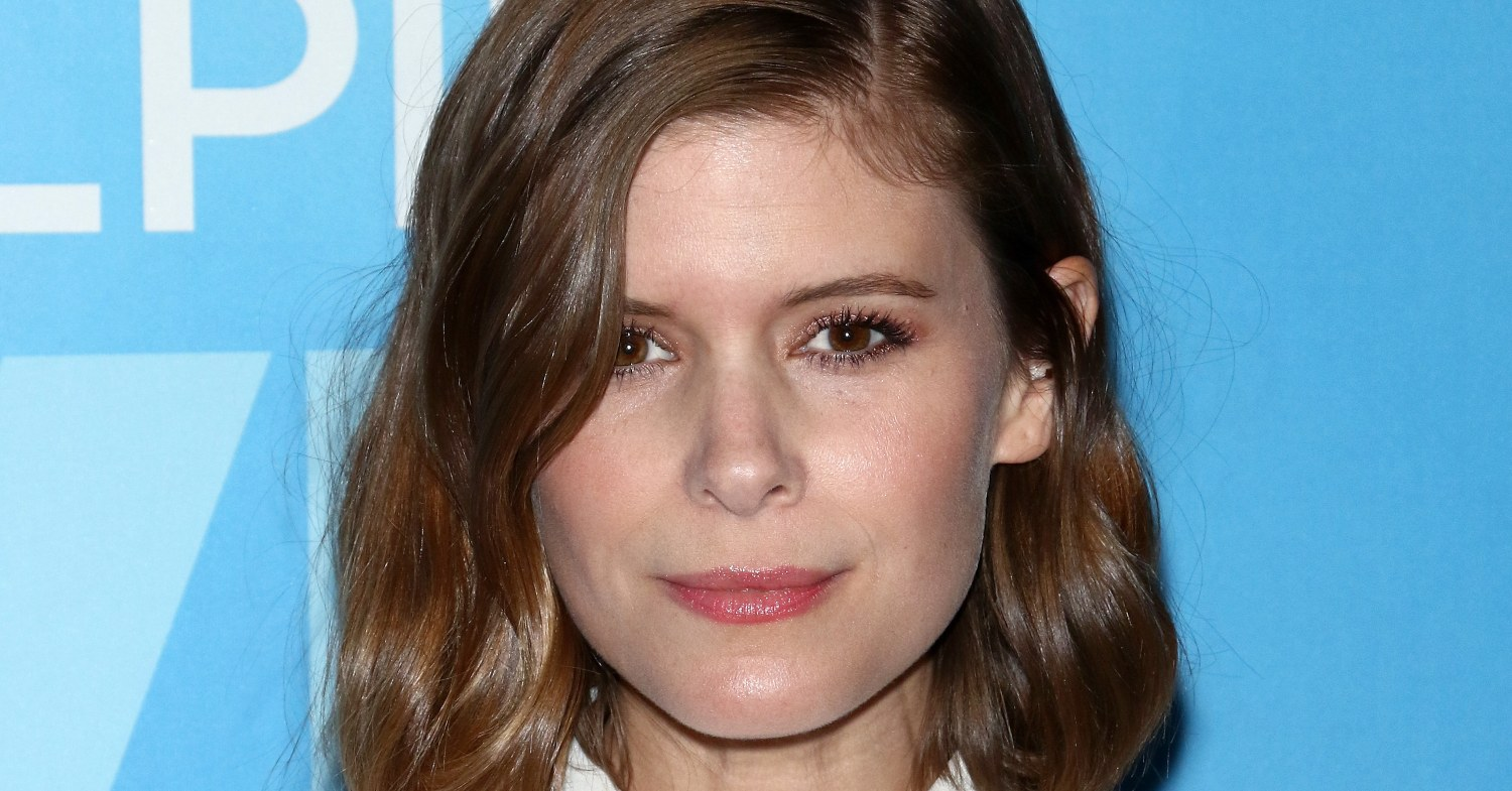 Kate Mara stands against a blue background at an event