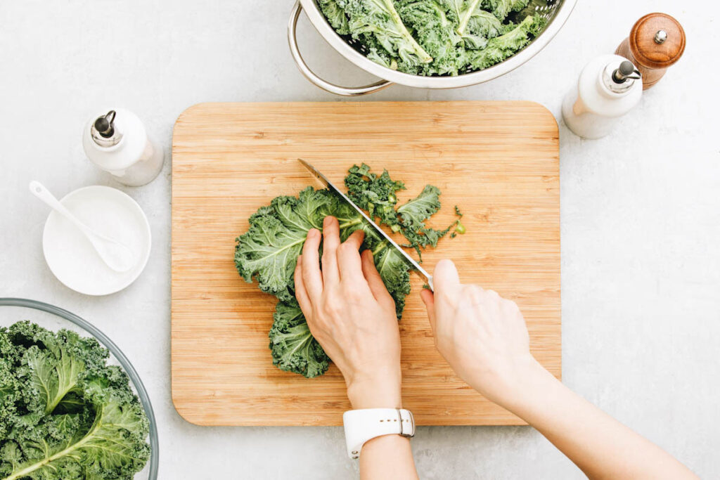 Close up image of someone's hands as they chop kale.