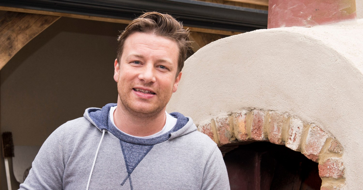Jamie Oliver stood in front of a pizza oven