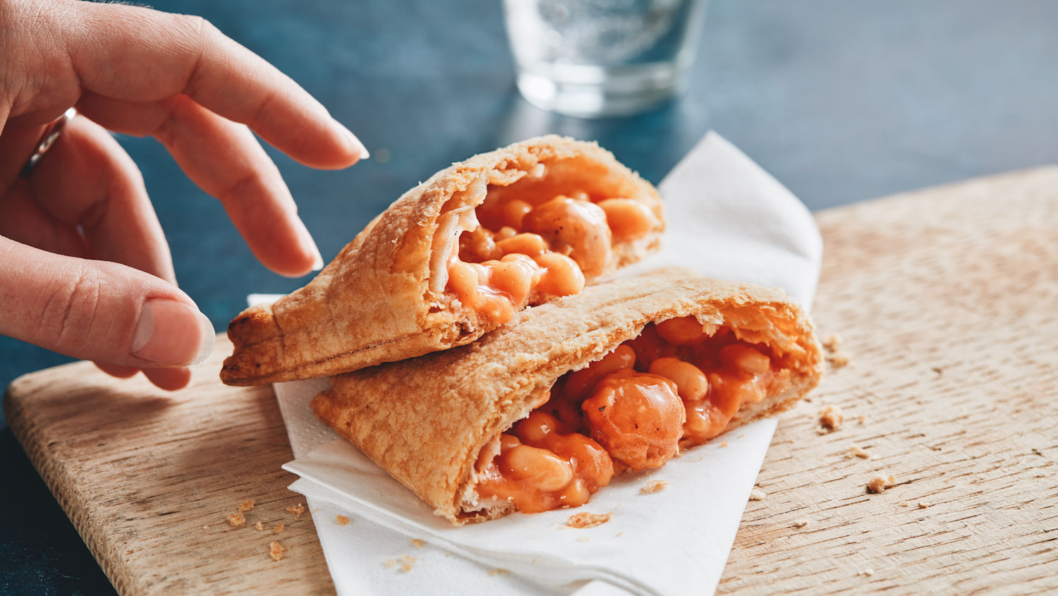 Photo of someone reaching their hand towards Greggs' new vegan Sausage, Bean, and Cheese Melt, cut in half to expose the filling.