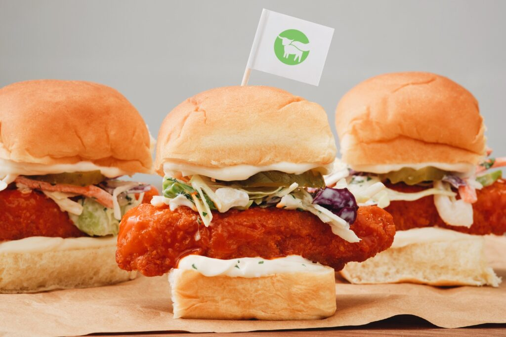 Beyond Meat's vegan chicken tenders in burger buns with pickles, salad, and wing sauce, featuring a Beyond flag and a grey background.