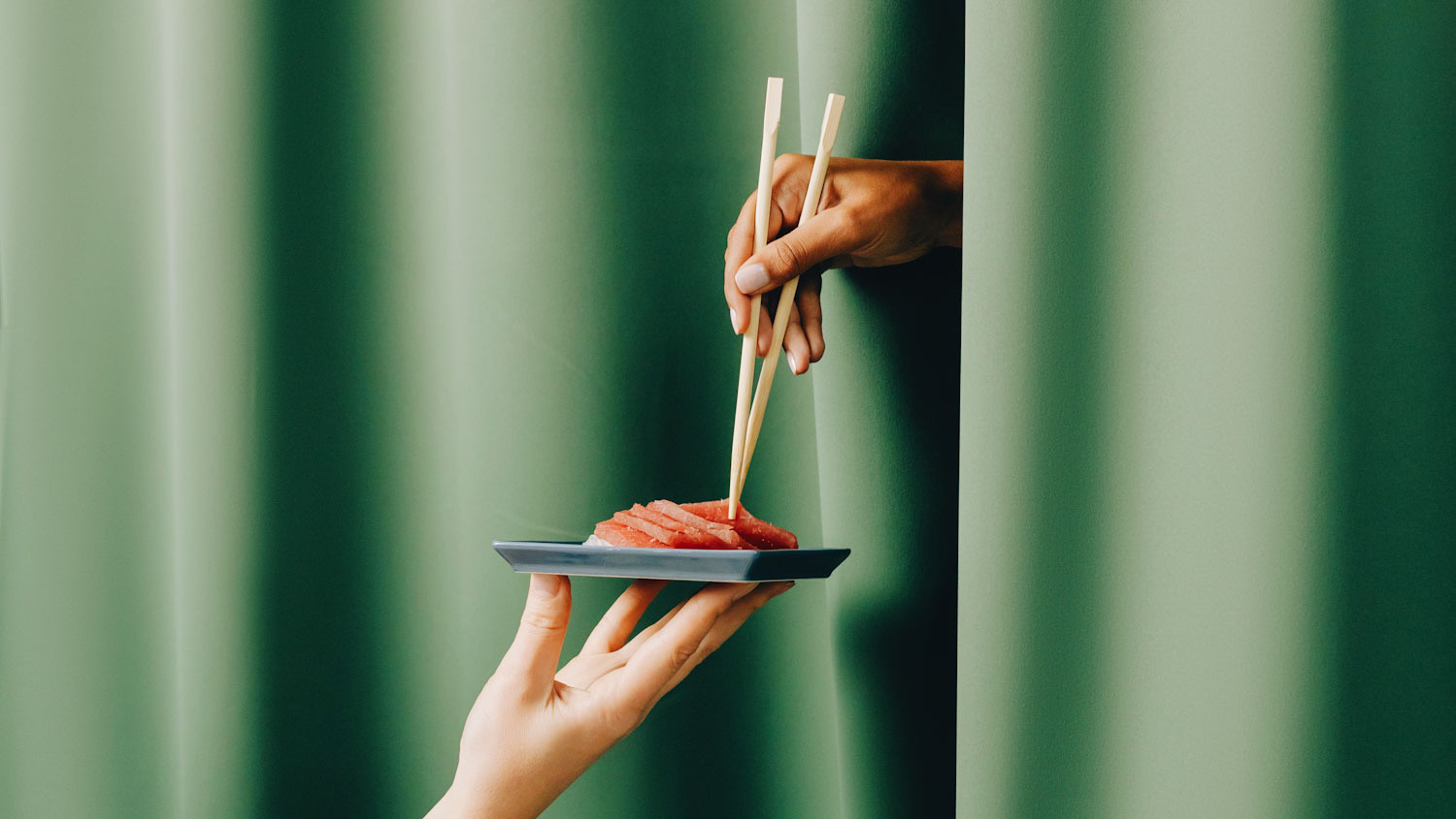 What is a cultured sushi tasting room? Image shows a hand holding up a plate of sushi with another hand emerging from a green curtain with chopsticks.