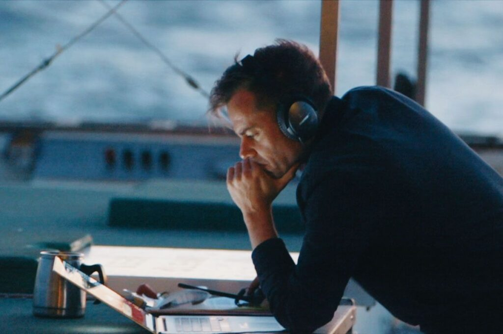 Director Joshua Zeman looking at a laptop with headphones on, on a boat during his search for the loneliest whale.