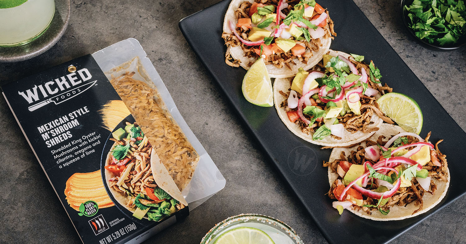 Photo of Wicked Kitchen's Mexican-style M'Shroom Shreds, including both packaging and some plated up soft-shell tacos.
