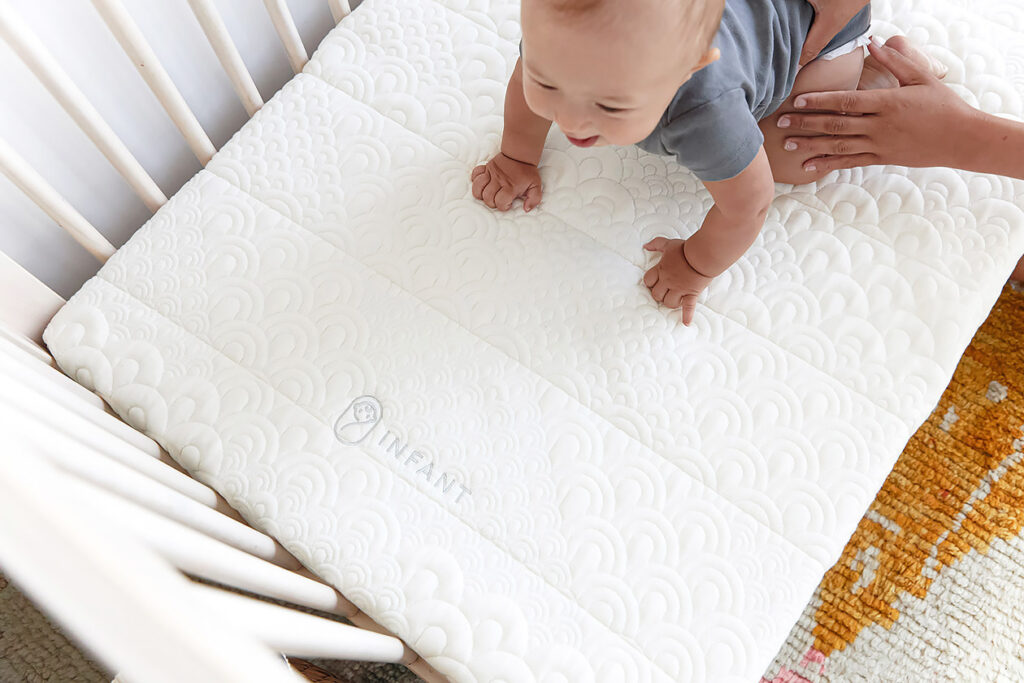 Photo shows a baby playing on the Brentwood Home crib mattress.