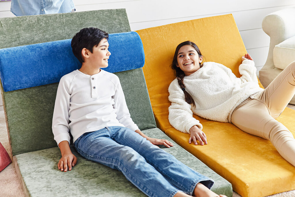 Photo shows two children laying on the Brentwood Home eco couch.