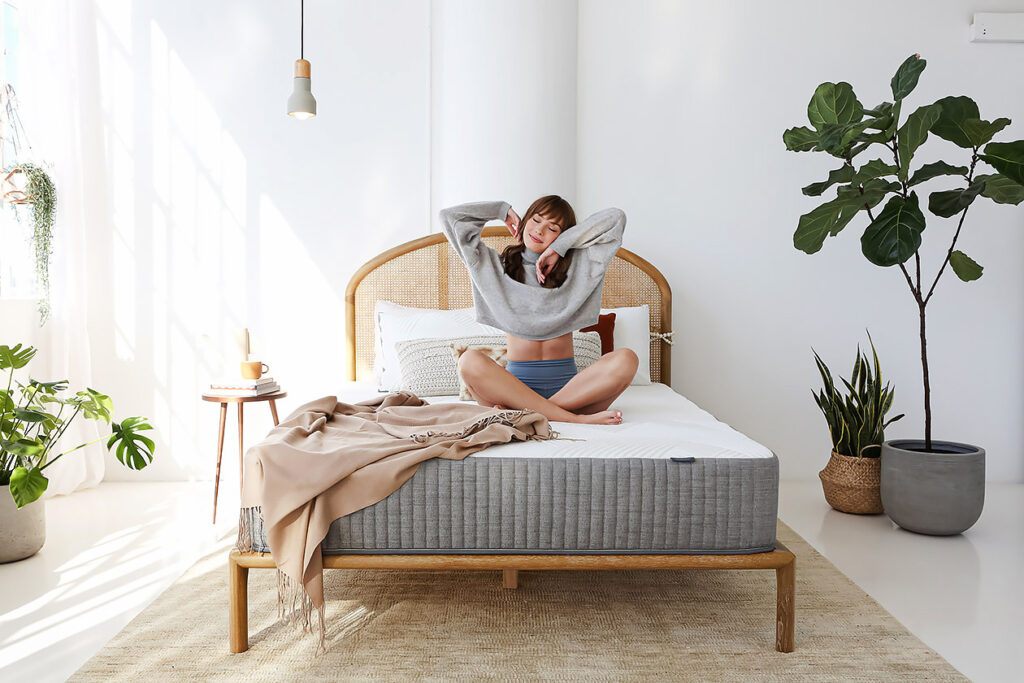 Photo shows a woman sitting on an unmade bed stretching.