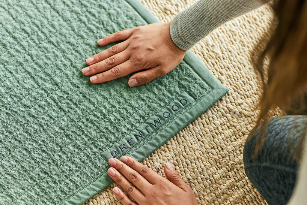 Close-up photo of someone's hands resting on the edge of a yoga mat. Physical self care can also help reduce stress—and improve sleep.