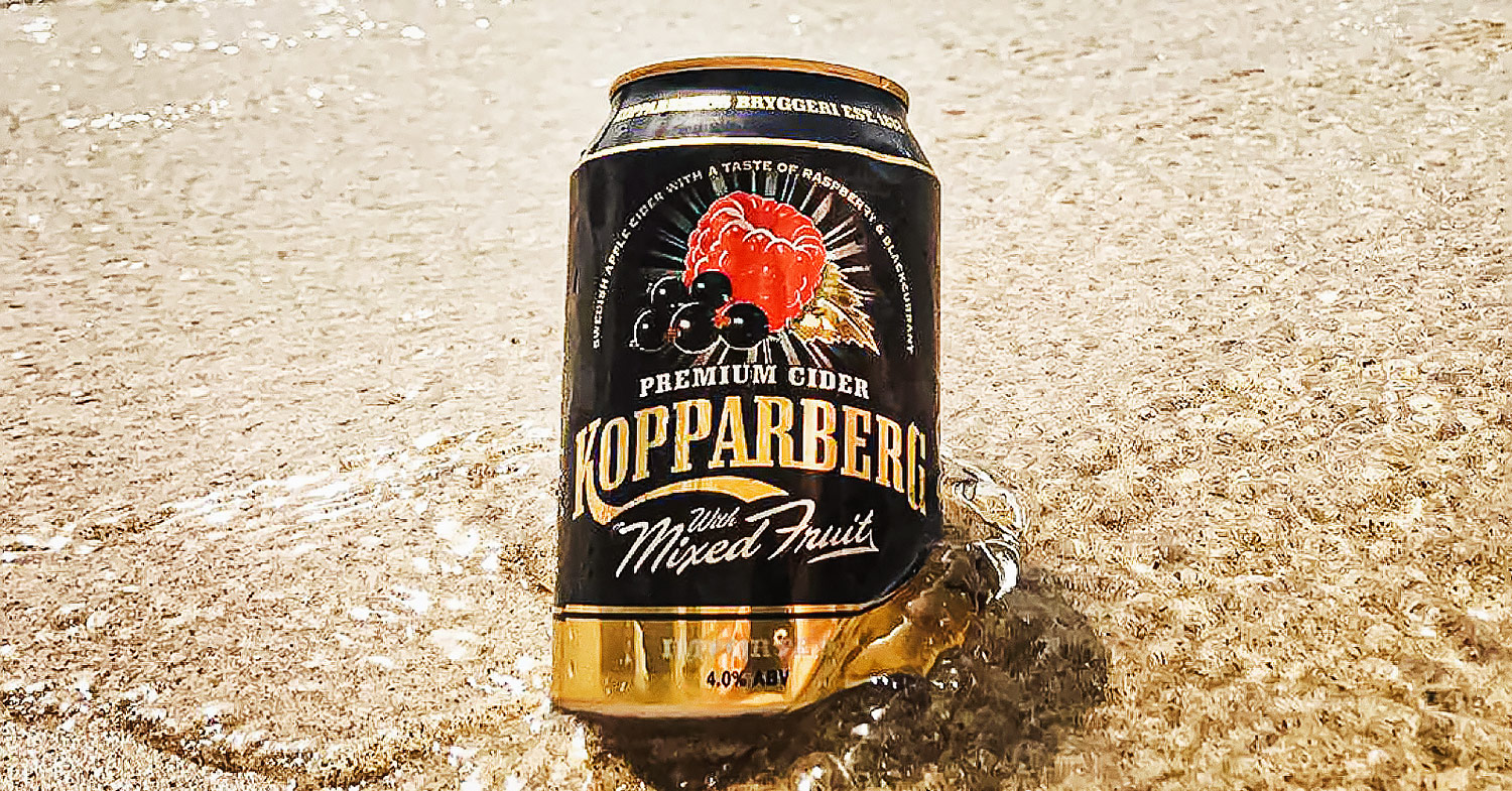Photo of Kopparberg Mixed Fruits cider (which is now vegan) in the water at the beach.
