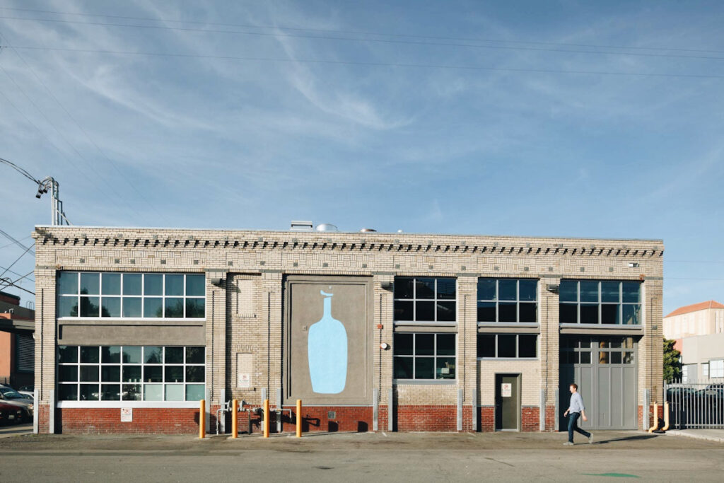 Photo of the front of a Blue Bottle Coffee shop and roastery. All the brand's branches now serve oatPhoto of the front of a Blue Bottle Coffee shop and roastery. All branches now serve oat milk. milk.