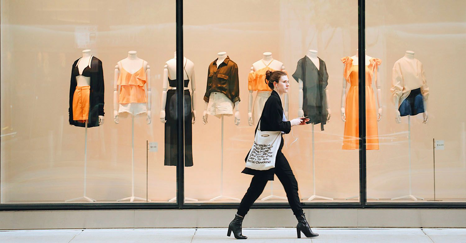 A woman walks down a high street past a clothing store