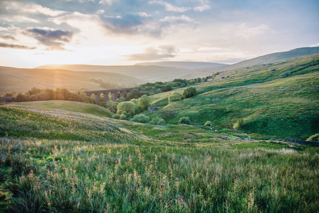 Photo features rolling green hills and an aquaduct of the kind common in England and the UK.