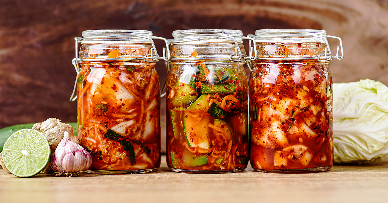Close-up image of three full mason jars filled with fermented vegetables.
