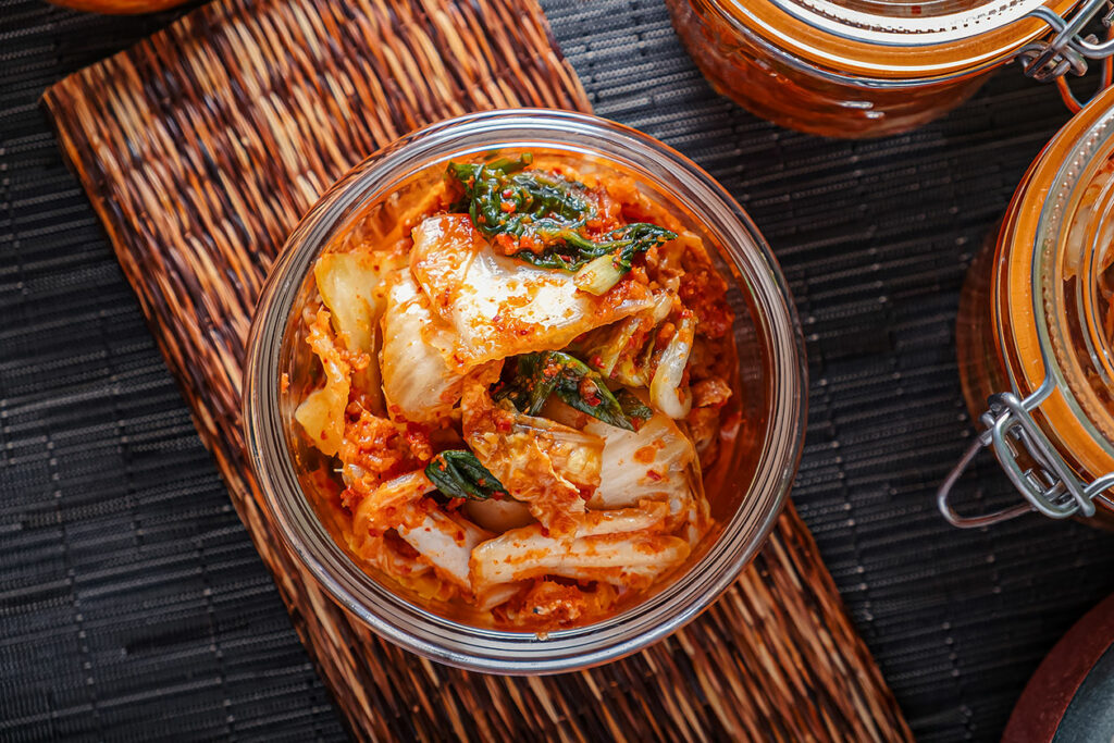 Bowl of spiced kimchi on a wicker mat.