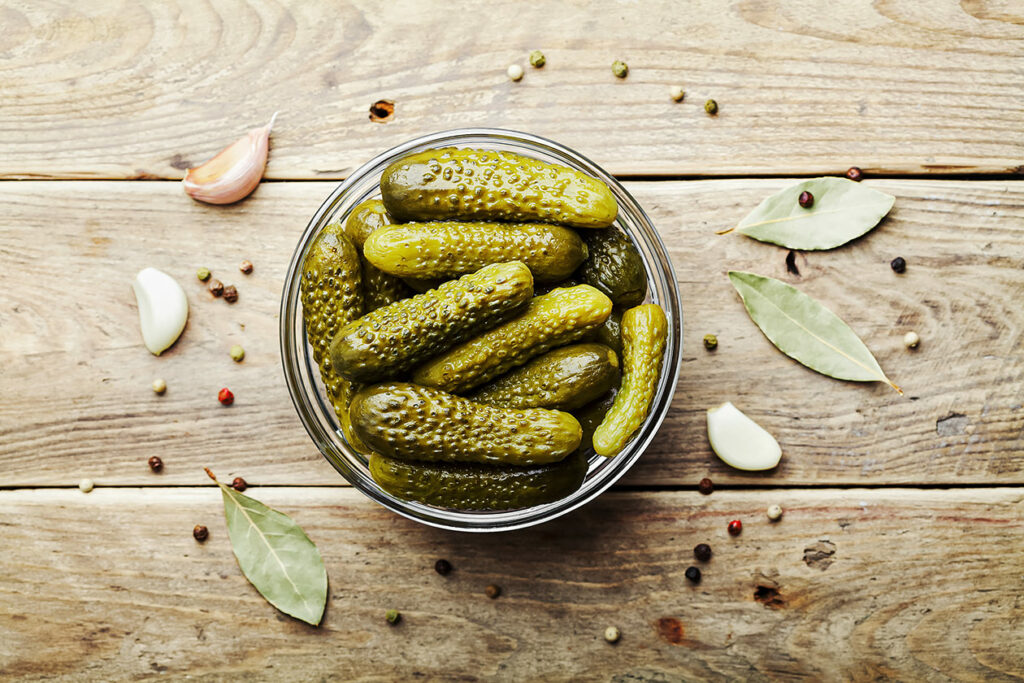 Photo features a bowl of pickled gherkins, surrounded by whole peppercorns, bay leaves, and garlic cloves.