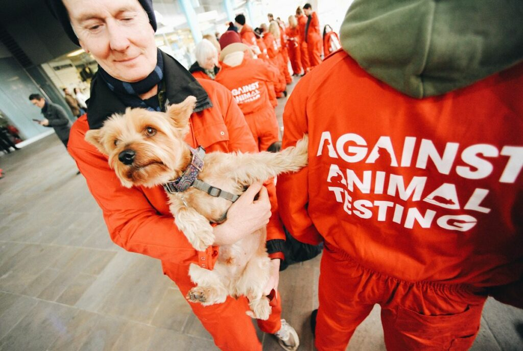 A man holding a dog at a cosmetic animal testing protest