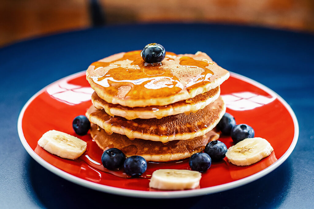 Photo of pancakes with syrup, blueberries, and banana. Patriots lineman Lawrence Guy is going vegan bit by bit, and enjoys pancakes for breakfast.