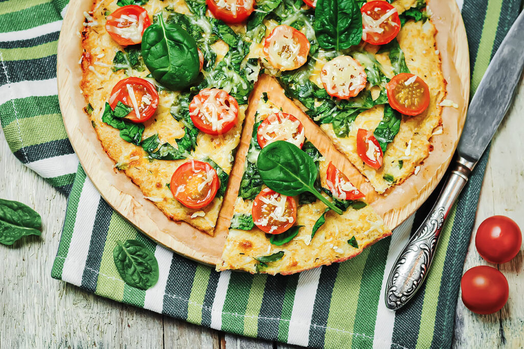 Photo of a light pizza topped with spinach, basil, and tomatos.