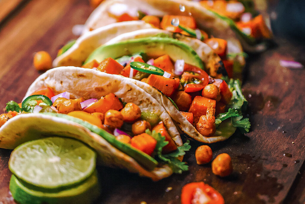 Photo of vegetable-filled tacos with lime, coriander, and avocado.
